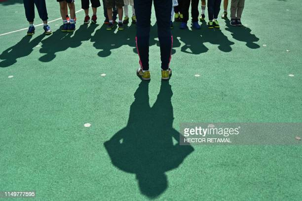 In this picture taken on June 6 students of Kangcheng kindergarten listen to a teacher during a football training session at their school in Minhang...