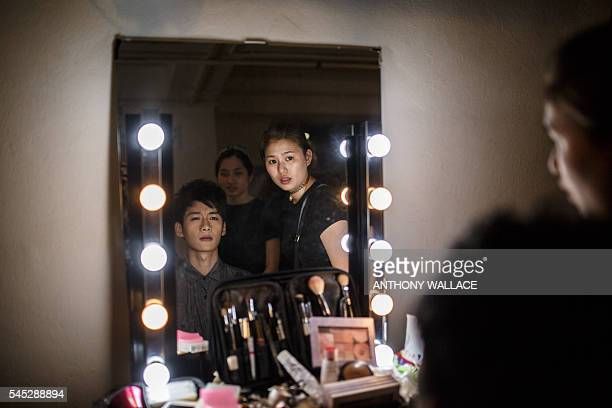 In this picture taken on June 7 a makeup artist helps prepare an actor before he performs on the set of recent 24 year old graduate Crosby Yip's...