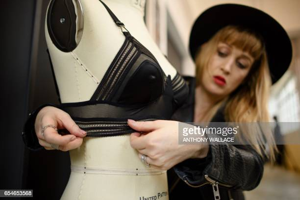 In this picture taken on March 10 Jasmine Smith founder of lingerie firm Raven Rose adjusts one of her creations on a mannequin while posing during a...