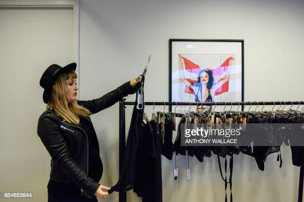 In this picture taken on March 10 Jasmine Smith founder of lingerie firm Raven Rose looks at one of creations while posing during a portrait session...