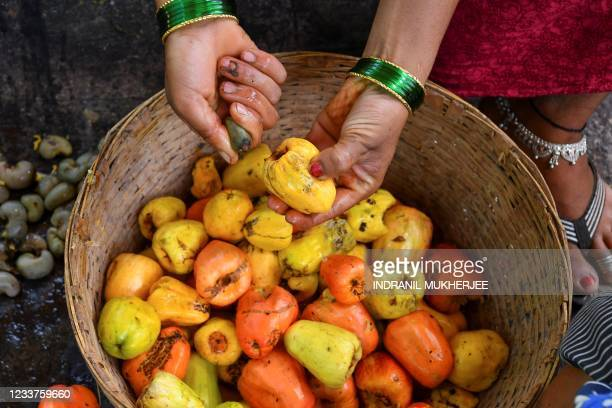 In this picture taken on March 13 a worker separates cashew nuts from apples at a farm belonging to the Madame Rosa distillery at Pilerne in North...