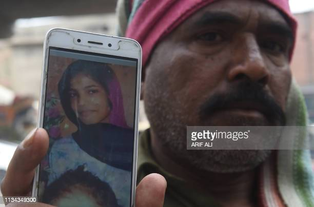 In this picture taken on March 14 Muhammad Riaz father of 16yearold Uzma a maid who was found dumped in a city canal shows her picture on a...