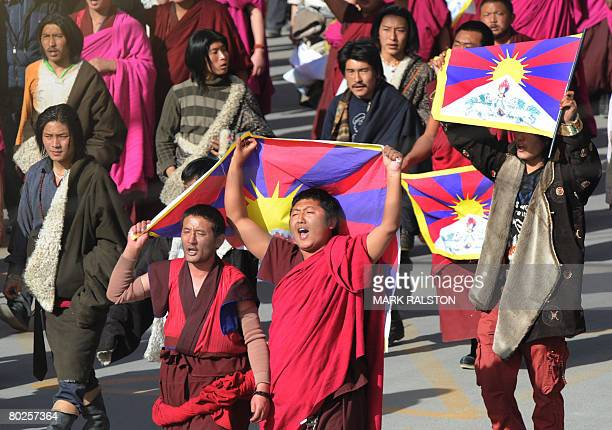 In this picture taken on March 14 protesters led by Tibetan Buddhist monks shout slogans and carry the Tibetan national flag after being blocked by...