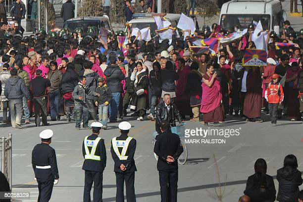 In this picture taken on March 14 Protesters led by Tibetan Buddhist monks are blocked by riot police as they shout slogans and carry the Tibetan...