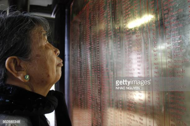 In this picture taken on March 15 local resident Truong Thi Hong looks at the names of relatives killed during the My Lai massacre at the war...