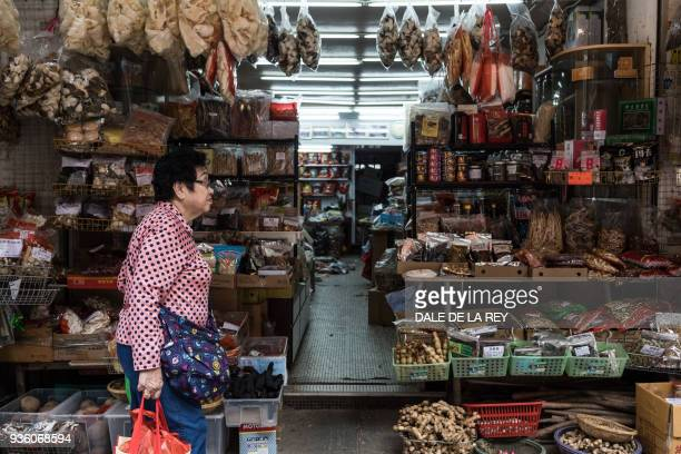 In this picture taken on March 17 a woman walks past a shop on a street popular for dried foods used in traditional Chinese medicine and dishes in...