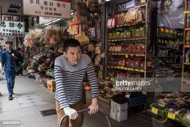 In this picture taken on March 17 a worker pushes a trolley past shops on a street popular for dried foods used in traditional Chinese medicine and...