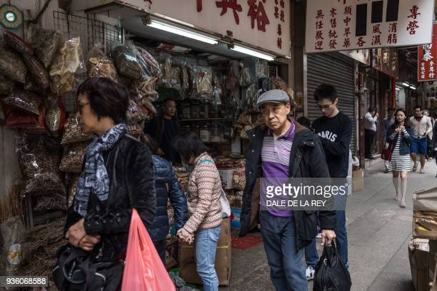 In this picture taken on March 17 people walk past shops on a street popular for dried foods used in traditional Chinese medicine and dishes in Hong...