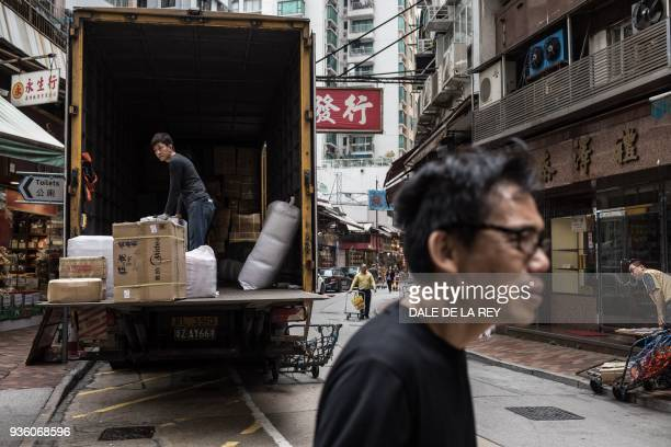 In this picture taken on March 17 workers deliver products to shops on a street popular for dried foods used in traditional Chinese medicine and...