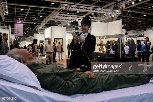 TOPSHOT In this picture taken on March 22 a woman takes photos of Chinese artist Shen Shaomin's Fidel Castro part of his 'Summit' project at Art...