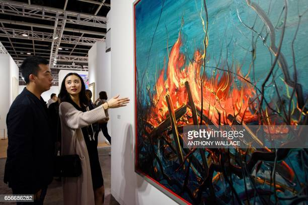 In this picture taken on March 22 Chinese investment banker Huang Xiaoshuai and his wife Wei Mengyuan chat in front of their newly acquired painting...