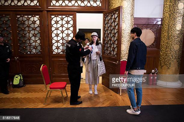 In this picture taken on March 30 Chinese model Xu Naiyu arrives at a security gate of the Beijing Hotel for a show at China Fashion Week in Beijing...