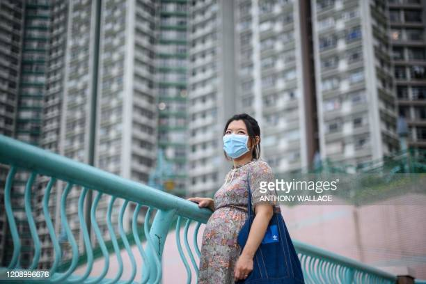In this picture taken on March 31 expectant mother Jamie Chui poses in front of residential buildings near where she lives in Hong Kong. - Jamie Chui...