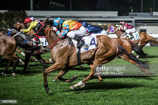In this picture taken on March 31 jockeys compete on their horses during the night horse races at the Hong Kong Jockey Club in the Happy Valley...