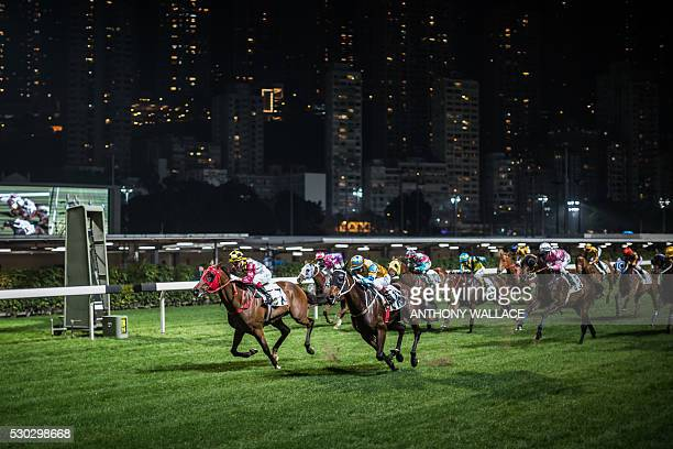 In this picture taken on March 31 jockeys ride their horses as they compete during a night horse race at the Hong Kong Jockey Club in the Happy...