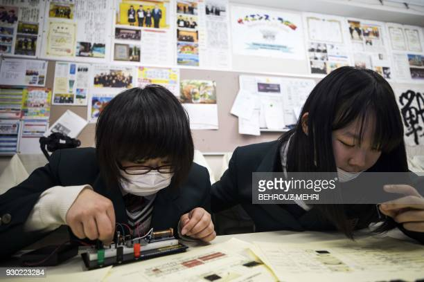 In this picture taken on March 6 schoolgirls assemble a geiger counter kit by the Safecast nongovernmental organisation to measure the radiation in a...