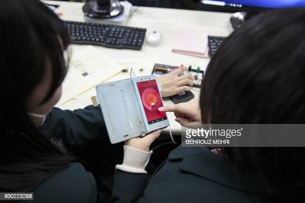 In this picture taken on March 6 schoolgirls check an application connected to the geiger counter kit by the Safecast nongovernmental organisation to...