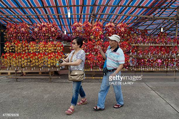 In this picture taken on May 10 a couple walk past a stall selling wind chimes at Joss House temple to celebrate the Tin Hau festival in Hong Kong...