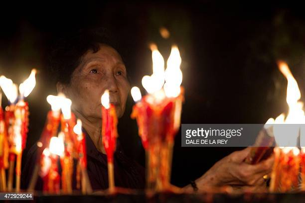 In this picture taken on May 10 a woman burns incense sticks at Joss House temple to celebrate the Tin Hau festival in Hong Kong Worshippers visit...
