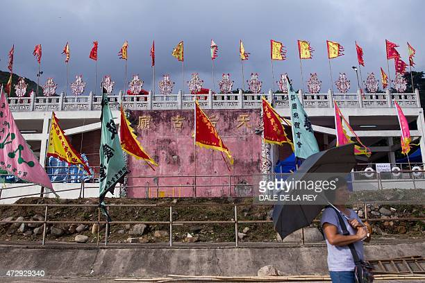 In this picture taken on May 10 a woman poses for a photograph in front of Joss House temple to celebrate the Tin Hau festival in Hong Kong...