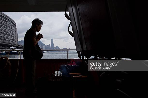 In this picture taken on May 10 a woman prays onboard a ferry sailing to Joss House temple to celebrate the Tin Hau festival in Hong Kong Worshippers...