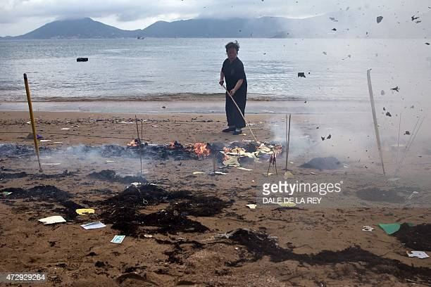 In this picture taken on May 10 a worker burns offerings on a beach at Joss House temple to celebrate the Tin Hau festival in Hong Kong Worshippers...