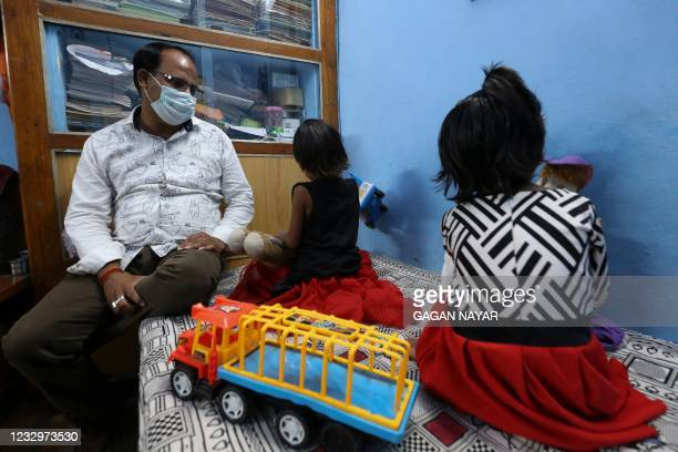 In this picture taken on May 11 twin sisters Tripti and Pari, who lost both their parents due to the Covid-19 coronavirus, play with their toys as a...