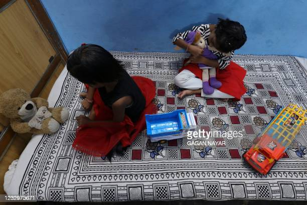 In this picture taken on May 11 twin sisters Tripti and Pari, who lost both their parents due to the Covid-19 coronavirus, play with their toys at a...
