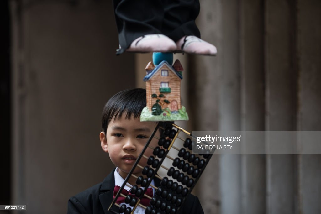 In this picture taken on May 12, 2018 a young boy stands on a float behind an abacus and a house, representing the city's housing situation, beneath another participant secured to a structure during a parade rehearsal ahead of the annual Cheung Chau bun festival in Hong Kong. - Children dressed as famous figures from ancient gods to political leaders floated above crowds of revellers on the island of Cheung Chau on May 22 in what has become one of Hong Kong's best-loved traditions to celebrate Buddha's birthday.