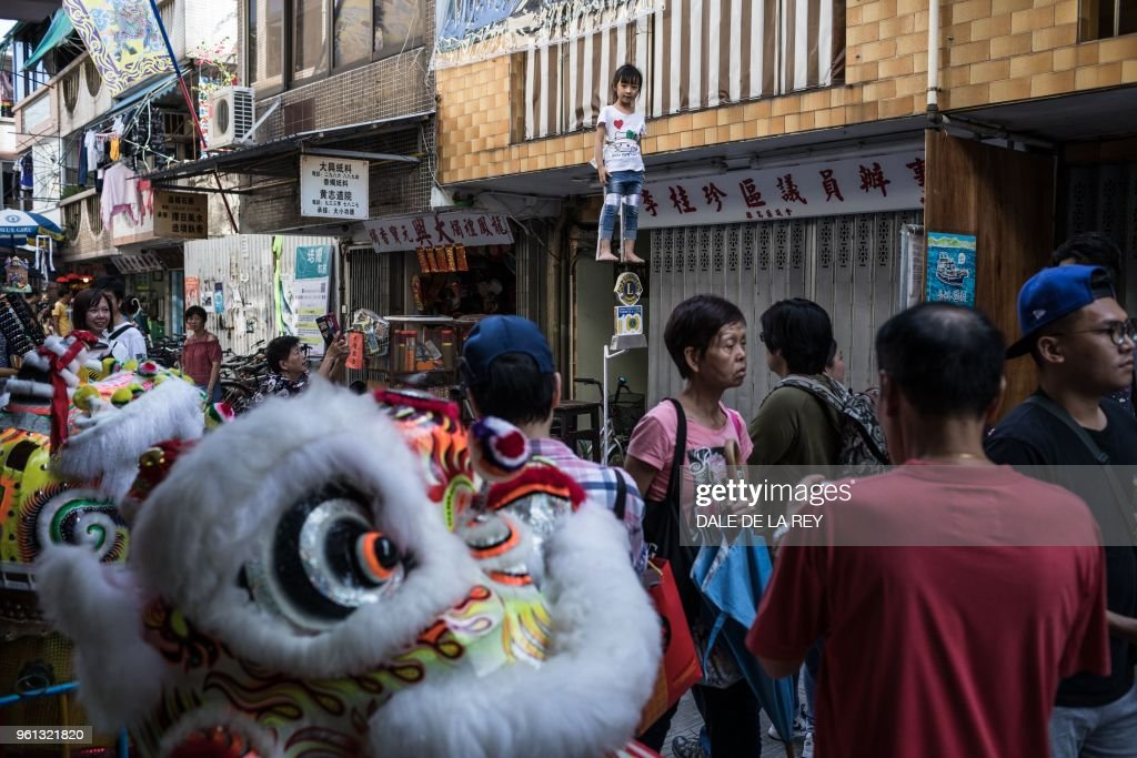 In this picture taken on May 12, 2018 people walk past a young girl secured to a float during a parade rehearsal ahead of the annual Cheung Chau bun festival in Hong Kong. - Children dressed as famous figures from ancient gods to political leaders floated above crowds of revellers on the island of Cheung Chau on May 22 in what has become one of Hong Kong's best-loved traditions to celebrate Buddha's birthday.