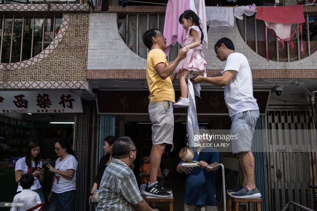 In this picture taken on May 12, 2018 two men secure a young girl to a float during a parade rehearsal ahead of the annual Cheung Chau bun festival in Hong Kong. - Children dressed as famous figures from ancient gods to political leaders floated above crowds of revellers on the island of Cheung Chau on May 22 in what has become one of Hong Kong's best-loved traditions to celebrate Buddha's birthday.