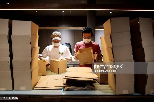 In this picture taken on May 13 2020 Hiromi Toyonaga and Shota Shiratori prepare cardboard boxes for delivery of their cricket ramen homecooking kits...
