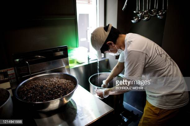 In this picture taken on May 13 2020 Yuta Shinohara cooks dried crickets used as an ingredient as part of cricket ramen homecooking kits at a kitchen...