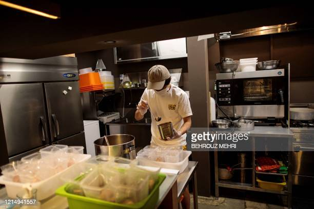 In this picture taken on May 13 2020 Yuta Shinohara ladles cricket sauce into plastic bags as part of cricket ramen homecooking kits at a kitchen in...