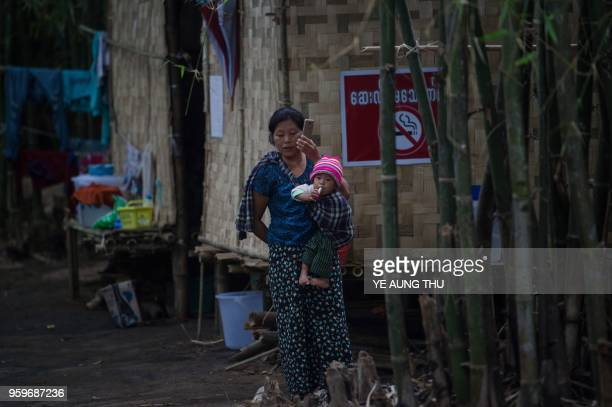 In this picture taken on May 13 an internally displaced woman with a child stand temporary shelter at a church compound in Myitkyina Kachin state...