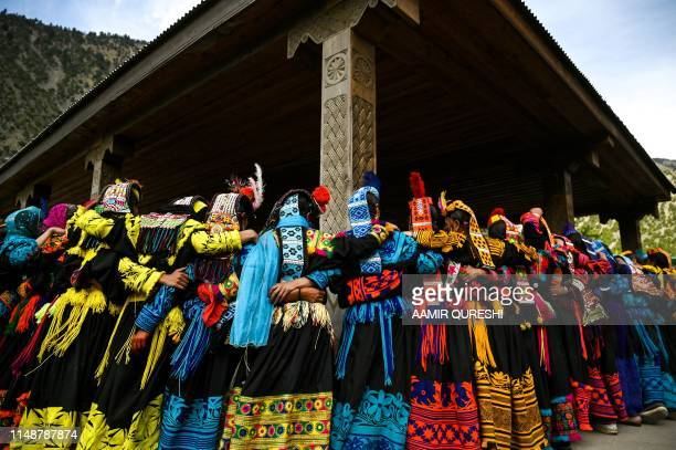In this picture taken on May 15 Kalash women wearing traditional dresses dance to celebrate 'Joshi', a festival to welcome the arrival of spring, at...