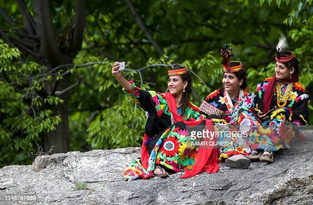 In this picture taken on May 16 a Kalash woman wearing a traditional dress takes a selfie with her friends during a break as they celebrate 'Joshi',...