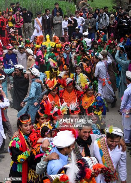In this picture taken on May 16 Kalash men and women wearing traditional dress dance as they celebrate 'Joshi' a festival to welcome the arrival of...