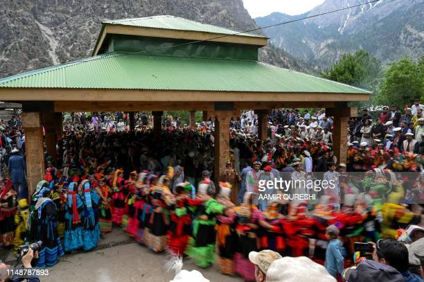 In this picture taken on May 16 Kalash women wearing traditional dresses dance as they celebrate 'Joshi' a festival to welcome the arrival of spring...
