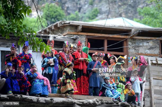 In this picture taken on May 16 Kalash women wearing traditional dresses gather in front of a house as they wait to celebrate 'Joshi', a festival to...