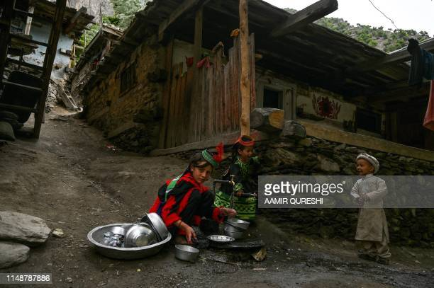 In this picture taken on May 17 Kalash girls wearing traditional dresses clean dishes outside their house after celebrating 'Joshi' a festival to...