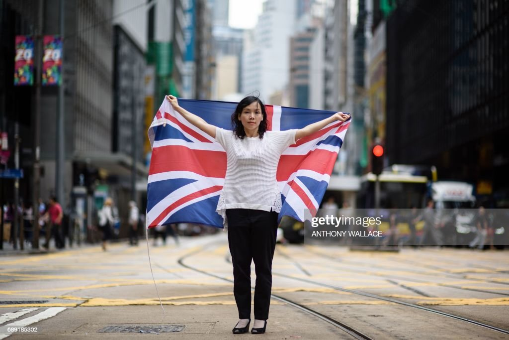 In this picture taken on May 18, 2017, artist and designer Alice Lai, 39, who heads a small protest group called HK-UK Reunification Campaign, holds the British national flag on a main road in Hong Kong. Lai regularly flies Hong Kong's former colonial flag at political rallies and heads a small protest group called HK-UK Reunification Campaign. 'Hong Kong and the UK coexisted in a proven, well-functioning system for close to two centuries,' says Lai. 'China is simply unfit to be governing Hong Kong -- it's a different way of thinking, a different way of life.' From its rattling trams and racecourses to its legal system and the ubiquitous consumption of Spam, Britain's colonial legacy still resonates through Hong Kong. But almost 20 years since the city was handed back to China under a deal that made it semi-autonomous, colonial emblems have become a symbol of protest. / AFP PHOTO / Anthony WALLACE / TO GO WITH Hong Kong-China-Britain-politics-history-culture-handover, FEATURE by Laura MANNERING