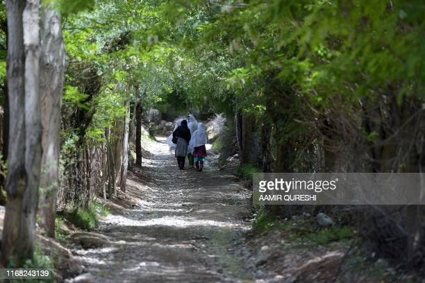 In this picture taken on May 18 Pakistani women walk on rural street in Booni village in Chitral Traditionally women have used rags and cloth to soak...