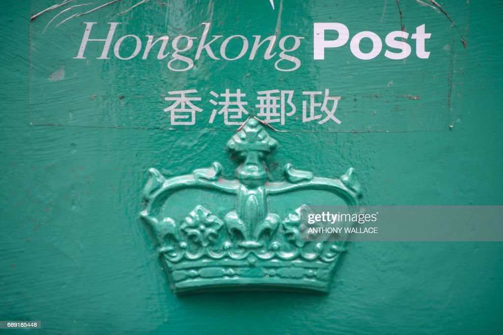 In this picture taken on May 18, 2017, royal British insignia is seen on a Hong Kong Post mail box in Hong Kong. Plans by the Hong Kong post office to cover up royal British insignia on mail boxes two years ago sparked outrage from conservation campaigners. From its rattling trams and racecourses to its legal system and the ubiquitous consumption of Spam, Britain's colonial legacy still resonates through Hong Kong. But almost 20 years since the city was handed back to China under a deal that made it semi-autonomous, colonial emblems have become a symbol of protest. / AFP PHOTO / Anthony WALLACE / TO GO WITH Hong Kong-China-Britain-politics-history-culture-handover, FEATURE by Laura MANNERING