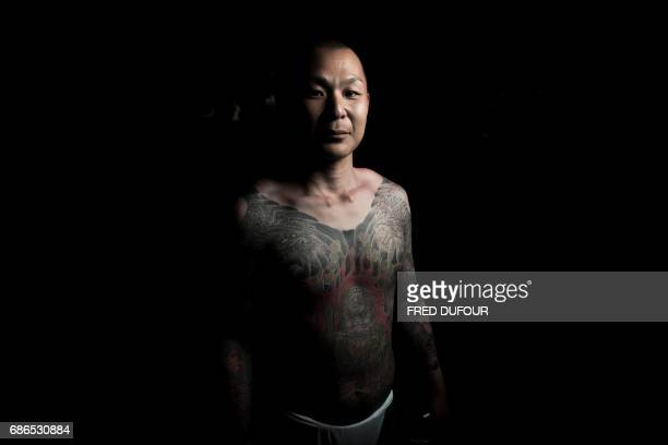 In this picture taken on May 20 a man poses for photographs showing his 'Irezumi' Japanese traditional tattoos related to the Yakuza's universe...