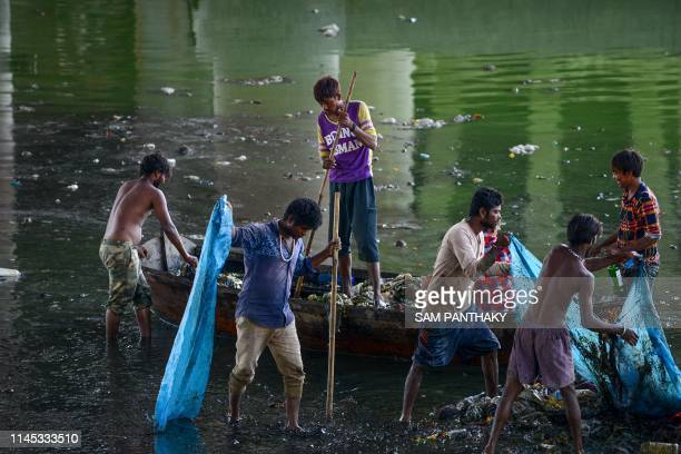 In this picture taken on May 20 Indian workers collect and remove trash as they take part in the cleaning of the Sabarmati river in Ahmedabad In...