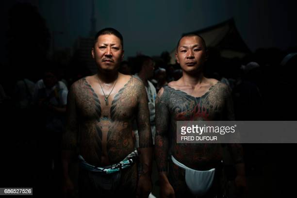 In this picture taken on May 20 men pose for photographs showing their 'Irezumi' Japanese traditional tattoos related to the Yakuza's universe during...