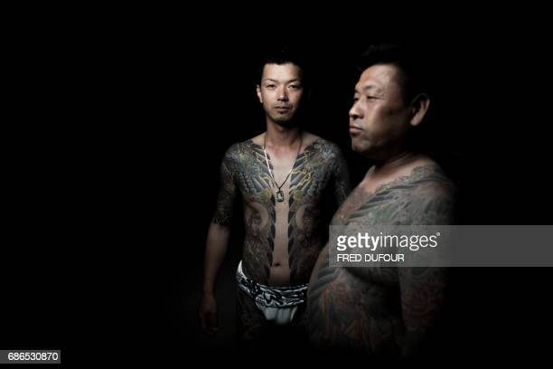 TOPSHOT In this picture taken on May 20 men pose for photographs showing their 'Irezumi' Japanese traditional tattoos related to the Yakuza's...