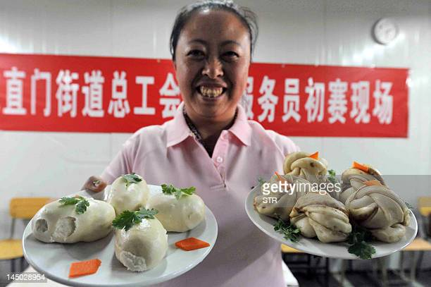 In this picture taken on May 22 a Chinese woman training to be a domestic maid shows the various dumplings she prepared during a vocational skills...