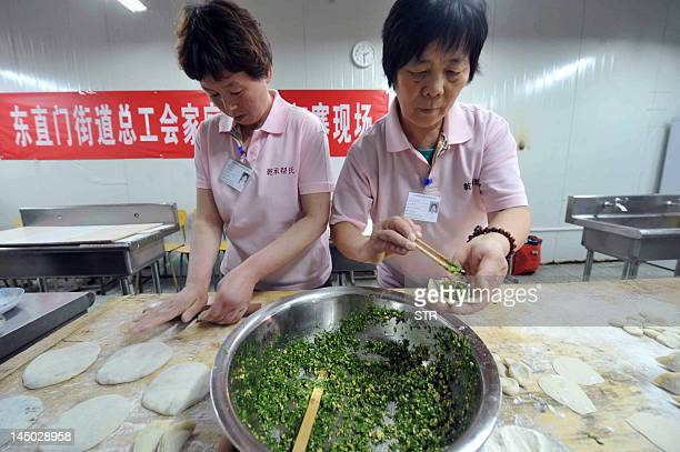 In this picture taken on May 22 Chinese women training to be domestic maids show how they make various dumplings during a vocational skills...